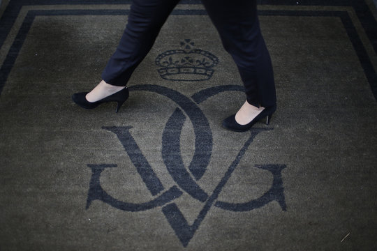An employee walks on a carpet past a logo at the luxury hotel Four Seasons George V in Paris