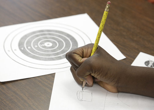 Sixth-grade student Nash-Haruna sketches a design for a cup that drops a marble on a target via a zip-line as Boeing employees mentor students at the after-school STEM academy held at Crestwood Elementary School in Covington, Washington