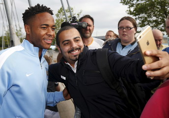 New Manchester City signing Raheem Sterling poses with supporters as he leaves the club's Etihad Stadium in Manchester, Britain
