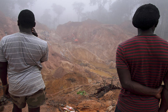 Suriname wildcat miners watch others dig to recover the bodies of seven miners who died when the 20-meter-high dirt wall of a gold mine collapsed, at Money Hill