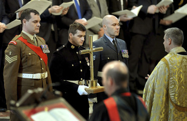 A cross made from used artillery shell cases is brought to the altar by servicemen during the Commemoration Service for Afghanistan at St Paul's Cathedral in London