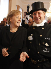 German Chancellor Merkel reactsb after she received a coin from chimney sweeper Mussner at the President's annual New Year's reception in Berlin