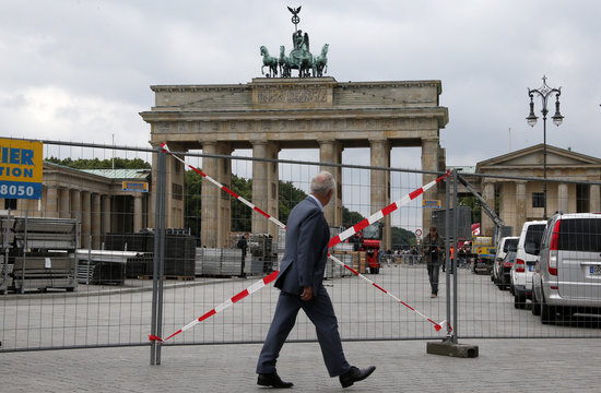 A man walks in front of barriers at the Brandenburg Gate where U.S. President Obama will give a speech during his visit in Berlin