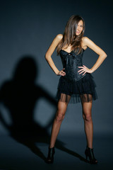 fashion style studio portrait of young beautiful and sexy woman, lady or female in black corset and skirt
