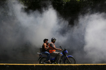 People on a motorcycle ride past as a truck is used to carry out fumigation to help control the spread of Chikungunya and dengue fever in Petare slum district of Caracas