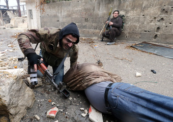 A Free Syrian Army fighter drags his comrade who was shot by sniper fire during heavy fighting in the Ain Tarma neighbourhood of Damascus