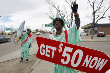 Manuel Martinez (R) and Jose, both dressed like the Statue of Liberty, wave signs advertising the Liberty Tax preparation business in Denver