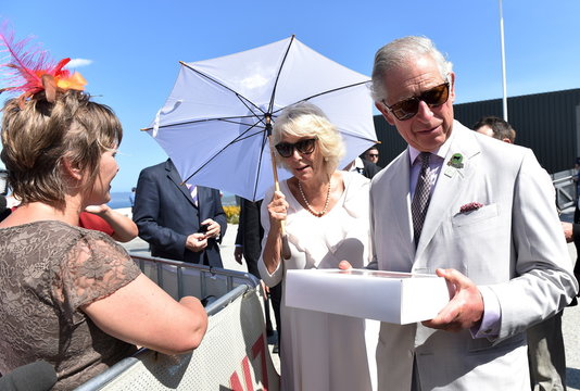 Britain's Prince Charles and his wife, Camilla the Duchess of Cornwall are given cup cakes with their picture on them during a visit to the National Anzac Centre in Albany,