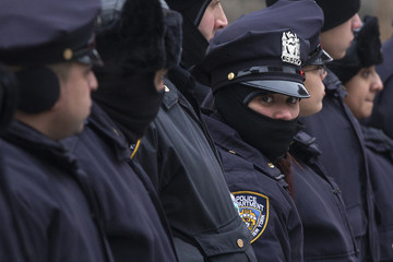 New York Police Department (NYPD) officers stand in a line before they search the site of a shooting in the Bronx borough of New York