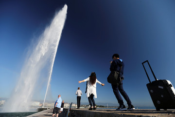 People take pictures in front of jet d'eau in Geneva