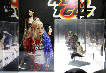 Women dressed in costumes look at figures of movie characters at Tokyo Comic Con at Makuhari Messe in Chiba