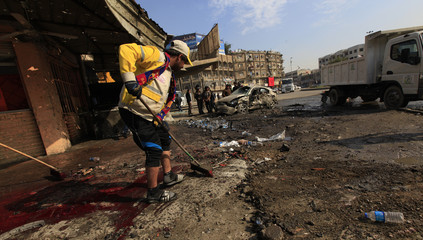 Municipality workers clean the site of a bomb attack in Baghdad