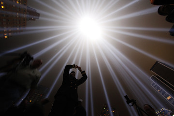"""A man takes pictures of the """"Tribute in Lights"""" in lower Manhattan on the 10th anniversary of the 9/11 attacks on the World Trade Center, in New York"""