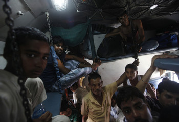 People from India's northeastern states, react to the camera as they sit inside an overcrowded train bound for the Assam state at a railway station in Kolkata