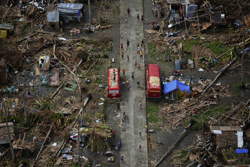 Survivors of Typhoon Haiyan wave as a U.S. military helicopter delivering aid flies over their isolated village north of Tacloban