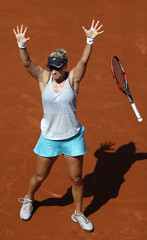 Mirjana Lucic-Baroni of Croatia celebrates after beating Simona Halep of Romania during their women's singles match at the French Open tennis tournament at the Roland Garros stadium in Paris