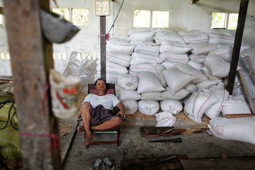 Than Lwin, a rice miller, takes a rest from work in Kyaiklat town