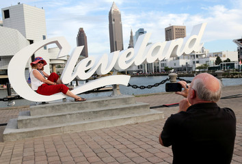 Donna Metz has her photo taken by husband Martin with the Cleveland skyline in the background during a Rock the Night kick off party on the sidelines of the Republican National Convention in Cleveland
