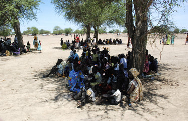 Internally displaced people sit under a tree in Turalei
