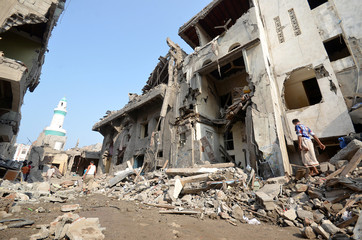 Man walks on the rubble of houses at the site of a Saudi-led air strike in the Red Sea port city of Hodeidah
