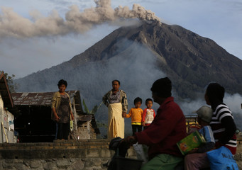 A family chats with their neighbour as they leave their house to temporary shelter with Mount Sinabung spewing ash in the background as seen from Tiga Pancur village in Karo