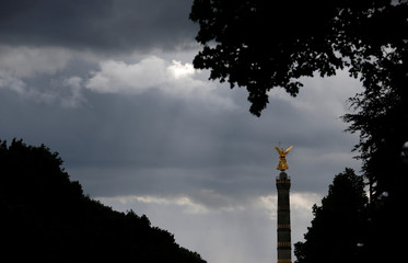 The 'Golden Victoria' monument on top of the victory column is silhouetted against a dark cloudy sky in Berlin