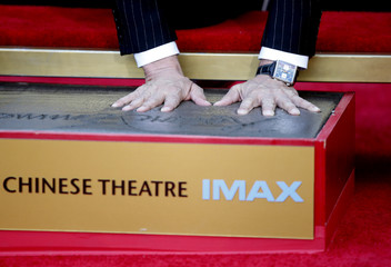 Director Roland Emmerich presses his hands into the cement during his Hand and Foot Print Ceremony in Hollywood