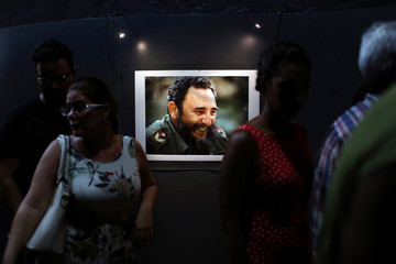 """People look at a picture of Cuba's former President Fidel Castro during the opening of the exhibition """"Fidel"""" in Havana, Cuba"""