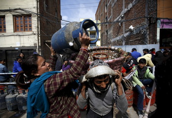A woman loads up her empty cylinders as she heads back empty-handed after finding out she would not be able to buy cooking gas, during the ongoing fuel crisis that has been continuing for over a month now, in Kathmandu