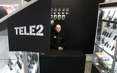 A shop assistant looks on from inside a Tele2 company's sales office in St. Petersburg