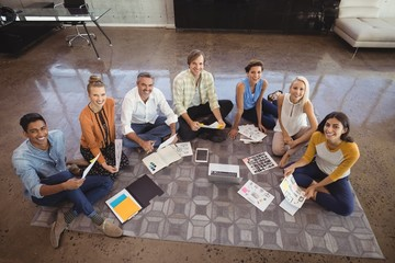 Creative business team sitting on floor in office
