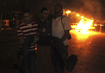 Protesters opposing Egyptian President Mohamed Mursi carry a wounded protester during clashes in front of the High Court in Cairo