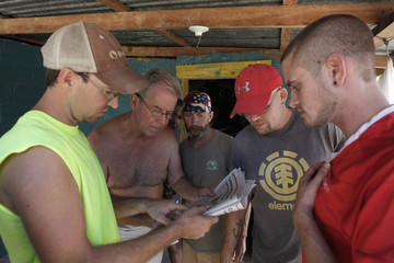 Crew members of Florida-based shipwreck salvage company Aqua Quest International Cook, Captain Mayne, Garrett, Matanich and Butler read a local newspaper article about themselves at the jail in Puerto Lempira