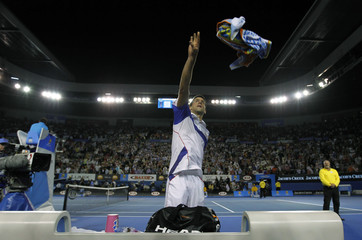Djokovic of Serbia throws his towel to the crowd after his semi-final victory over Federer of Switzerland at the Australian Open tennis tournament in Melbourne