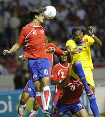 Costa Rica's Bryan Ruiz jumps for the ball with Ecuador's Cristian Suarez  during their international friendly soccer match in San Jose