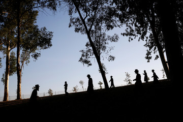 Ultra-Orthodox Jewish men are silhouette next to the Yarkon river as they perform the Tashlich ritual near the town of Petah Tikva, Israel