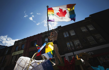A man holds a modified Canadian flag with Pride colours during the gay pride parade in Toronto