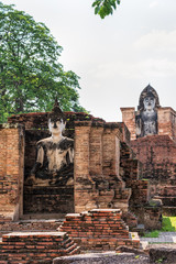 Ancient Buddha statue among the ruins under the bright sun of Wat Maha That temple in Sukhothai Historical Park is an old city and famous tourist attraction of Sukhothai Province, Thailand