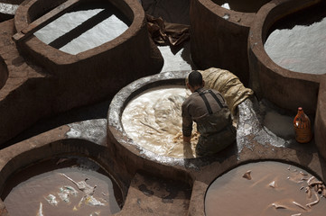 FEZ, MOROCCO - FEBRUARY 20, 2017: Unidentified men working within the paint holes at the famous Chouara Tannery in the medina of Fez, Morocco. The leather tannery dates back to the 11th century AD.