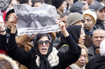 A woman holds a placard with an image of the late secular opposition leader Chokri Belaid during his funeral procession in the Jebel Jelloud district in Tunis