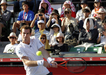 Andy Murray of Britain returns a shot to Stanislas Wawrinka of Switzerland in front of spectators shielding from the sun  during their men's singles quarter-finals match at the Japan Open tennis championships in Tokyo