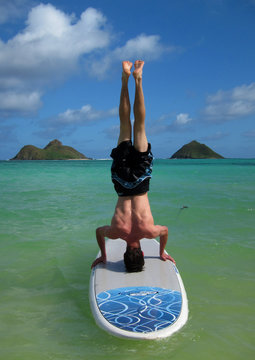 Tom Garrow does a headstand on his surfboard at Lanikai Beach in Kailua while on vacation in Hawaii