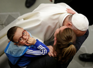 Pope Francis kisses the mother of a sick child as he leads the weekly audience in Paul VI hall at the Vatican