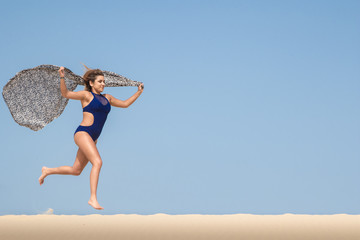 Pretty brunette running in the sand