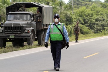 A policeman uses a mask on the Pan-American Highway, which is covered in ash from the San Cristobal Volcano