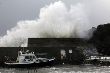 Waves break over the harbour wall in the town of Portstewart on the the north coast of County Londonderry as storm force winds batter the north coast of Northern Ireland with gales forecast to reach 80mph.