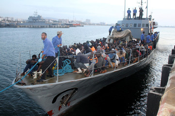 Migrants arrive by boat at a naval base after they were rescued by Libyan coastguard, in the coastal city of Tripoli