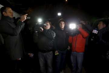 Journalists gather outside a police station in Buin outside Santiago