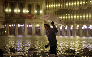 A man wades through flood waters in Saint Mark's square in Venice