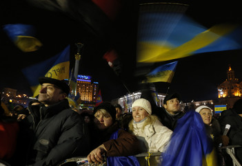 Pro-European integration protesters wave Ukranian flags during a rally in Independence Square in Kiev